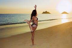 Junge Frau, die Yoga am Strand tut Stockbild