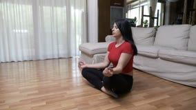 Junge Frau, die Yogaatemgymnastik tut und in Lotussitz auf dem Boden meditiert stock video footage