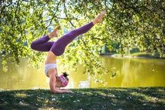 Junge Frau, die Yogabalance im Park nahe See tut Stockfoto