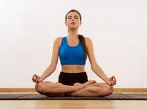 Junge Frau, die Yogalotussitz tut lizenzfreie stockbilder