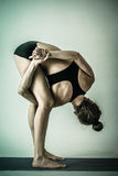 Junge Frau, die Yogatorsion durchführt stockbilder