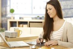 Junge Frau, die Zeichnungsauflage verwendet Lizenzfreies Stockfoto
