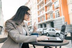 Junge Frau, die Zeigefinger herauf das Schauen in eine Laptop-Computer gestikuliert Aufmerksamkeit, Idee, Eureka stockbilder