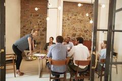 Junge Frau, die zu einer Teambesprechung in einem Sitzungssaal spricht lizenzfreie stockfotos