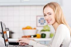 Junge Frau, die zu Hause eine Laptop-Computer verwendet lizenzfreies stockfoto