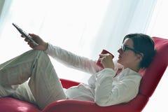 Junge Frau, die zu Hause fernsieht stockfotografie