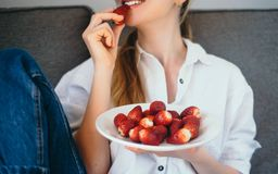 Junge Frau, die zu Hause gesunde Lebensmittel srawberries, gesundes cle isst lizenzfreies stockbild
