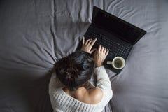 Junge Frau, die zu Hause an Laptop arbeitet Stockfoto