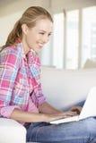 Junge Frau, die zu Hause Laptop-Computer verwendet Lizenzfreies Stockbild