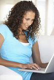 Junge Frau, die zu Hause Laptop-Computer verwendet Lizenzfreie Stockbilder