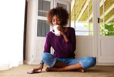Junge Frau, die zu Hause mit Kaffee und Handy sitzt Lizenzfreies Stockbild