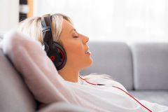 Junge Frau, die zu Hause Musik auf Kopfhörern hört Stockfoto