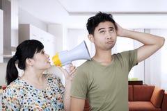 Junge Frau, die zu Hause zu seinem Ehemann schreit stockbild