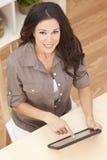 Junge Frau, die zu Hause Tablette-Computer verwendet Stockbilder