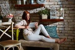 Junge Frau, die zu Hause Tablette verwendet stockbild