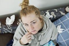 Junge Frau, die zu Hause unter Kälte und Grippe leidet Stockbild