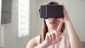 Junge Frau, die zu Hause VR-virtuelle Realität 360 Gläser verwendet Machend grasen Sie, summen Sie laut und klopfen Sie Gesten stock video