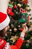 Junge Frau, die zu Hause Weihnachtsbaum mit Zuckerstangen, Sankt-Hut tragend verziert Vorbereiten zum neuen Jahr stockfoto