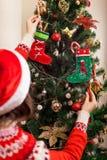 Junge Frau, die zu Hause Weihnachtsbaum mit Zuckerstangen, Sankt-Hut tragend verziert Vorbereiten zum neuen Jahr stockfotos