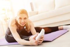 Junge Frau, die zu Hause Yoga tut Stockbilder