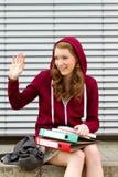 Junge Frau, die zu ihren Freunden wellenartig bewegt Stockfotos