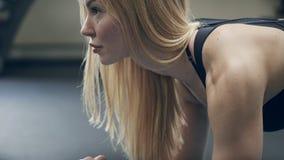 Junge Frau, die zuhause Übungsplanke auf Boden in der Turnhalle tut stock footage