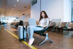 Junge Frau, die zuhause einen Laptop auf Schreibentastatur des Scho?es im Flughafen h?lt lizenzfreies stockfoto