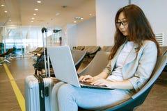 Junge Frau, die zuhause einen Laptop auf Schreibentastatur des Scho?es im Flughafen h?lt lizenzfreies stockbild