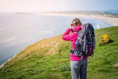 Junge Frau, die zum Abstand von Cliff Over The Seashore I schaut lizenzfreie stockfotos