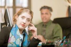 Junge Frau, die zum ahnungslosen Kollegen reagiert stockfotos