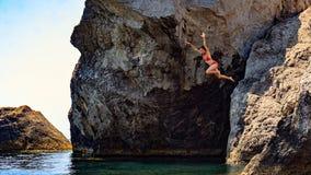 Junge Frau, die zum Meer von einer Klippe springt Lizenzfreies Stockfoto