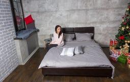 Junge Frau, die zurück beim Sitzen auf einem Bett und einem tragenden paja schaut Stockbild