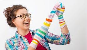 Junge Frau, die zwei bunte Socken hält stockfotos