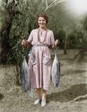 Junge Frau, die zwei enorme Fische hält (alle dargestellten Personen sind nicht längeres lebendes und kein Zustand existiert Lief lizenzfreie stockfotos