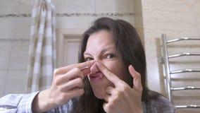 Junge Frau drückt heraus Pickel auf ihrer Nase und auf ihrem Gesicht zusammen stock video