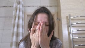 Junge Frau drückt heraus Pickel auf ihrer Nase und auf ihrem Gesicht zusammen stock footage