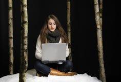 Junge Frau draußen im Schnee mit Laptop lizenzfreie stockfotos