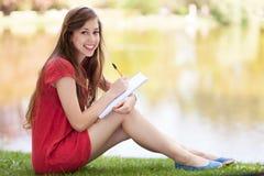 Junge Frau draußen mit Übungsteil und Bleistift stockbilder