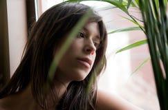 Junge Frau durch Plant und Fenster Lizenzfreie Stockfotografie
