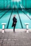 Junge Frau durch träumerisches Konzept des Swimmingpools Stockfotografie