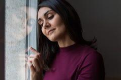 Junge Frau durchdacht am Fenster Stockfoto