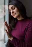 Junge Frau durchdacht am Fenster Stockfotografie