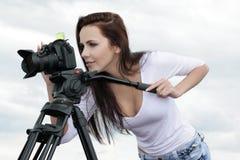 Junge Frau, ein Fotograf mit Kamera und Stativ Stockbild