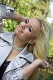 Junge Frau eine Blondine lächelt auf Bäumen eines Hintergrundes Stockfotos