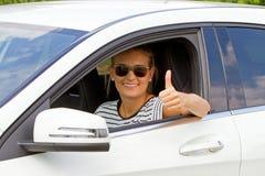 Junge Frau in einem Auto mit dem Daumen oben Stockfoto