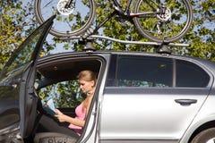 Junge Frau in einem Auto mit einer Karte in der Hand Lizenzfreie Stockfotos