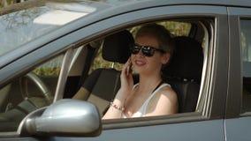 Junge Frau in einem Auto sprechend am Telefon stock video