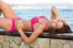 Junge Frau in einem Badeanzug, der auf einer Bank liegt Stockbilder