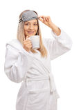 Junge Frau in einem Bademantel mit einer Schlafenmaske und einer Schale Lizenzfreie Stockbilder