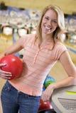 Junge Frau in einem Bowlingspielverbündeten Lizenzfreie Stockfotos